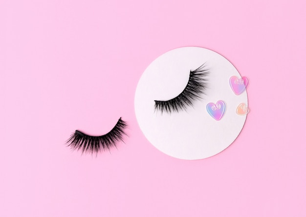 Creative layout with eyelashes. closed eyes on pastel pink background