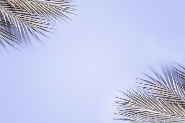 青い背景にキラキラシルバーのヤシの葉とクリエイティブなレイアウト