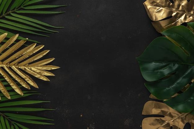 Креативный план с золотыми и зелеными тропическими пальмовыми листьями на черном фоне.