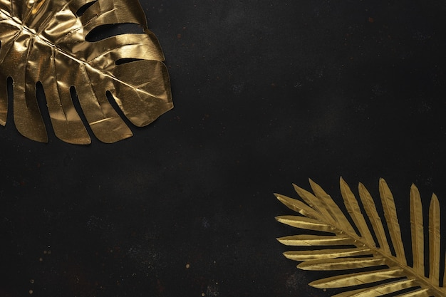 Creative layout with gold tropical palm leaves on black background.