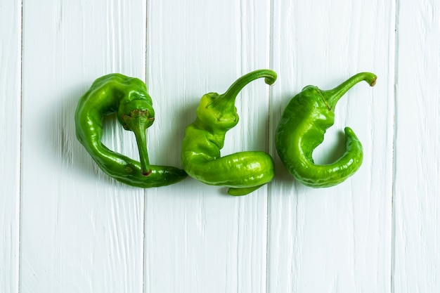 Creative layout with hot pepper and basil on a white wooden background with copy space.