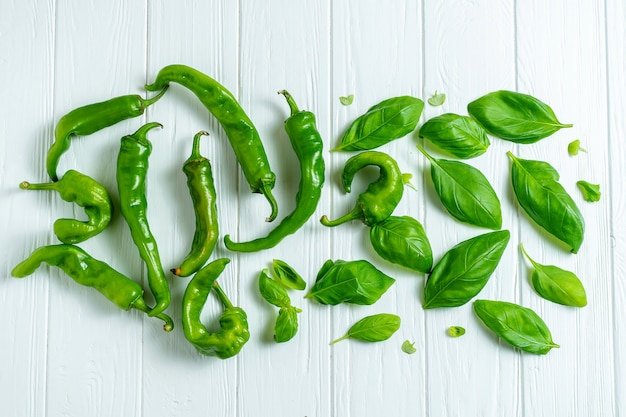 Creative layout with hot pepper and basil in on a white wooden background