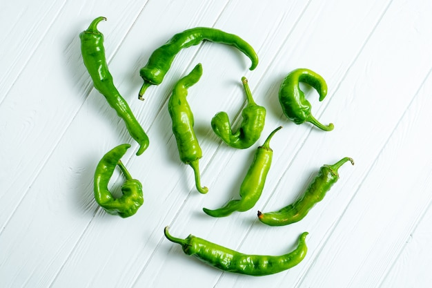 Creative layout with hot peppers in on a white wooden background with copy space.