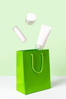 녹색 표면에 공중에 떠오르는 미용 제품과 종이 봉지가있는 창의적인 레이아웃. 바디 케어 미용 치료 개념. 스킨 케어 루틴