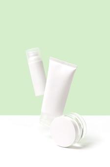 녹색 표면에 공중에 떠오르는 미용 제품으로 창의적인 레이아웃. 바디 케어 미용 치료 개념. 스킨 케어 루틴
