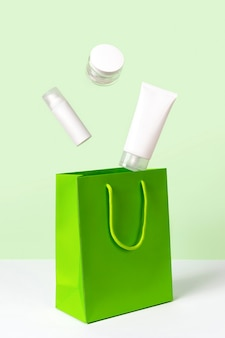 Creative layout with levitating beauty products and paper bag on green surface. body care beauty treatment concept. skincare routine