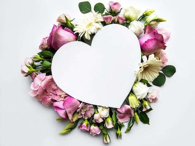 Креативный макет с розовыми цветами и формой сердца. юбилейная концепция. плоская планировка.