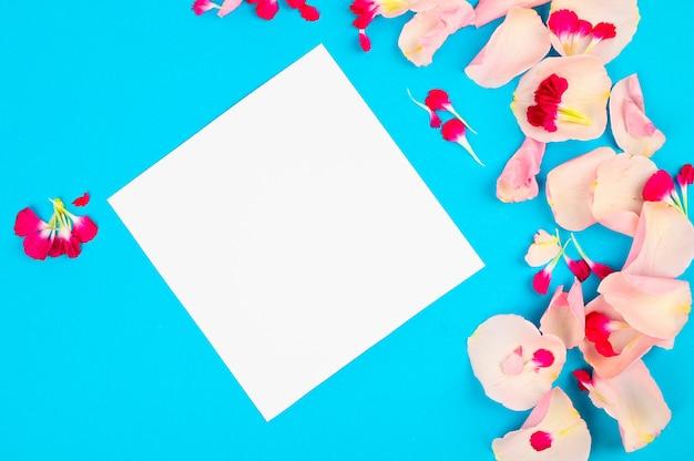 Креативный макет с розовыми лепестками на синем пространстве. пустая карточка скопируйте место для текста.