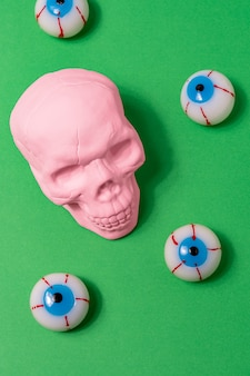 緑の背景にピンクの頭蓋骨と眼球の創造的なレイアウト