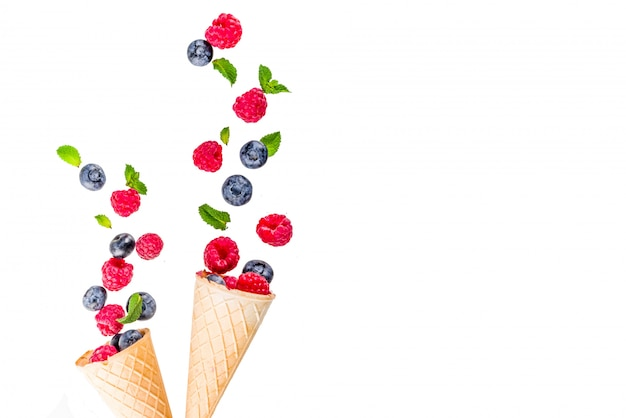 Creative layout with raspberry and blueberry with waffle ice cream cones, simple pattern aboveries