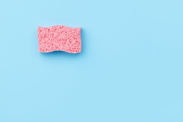 Creative layout with sponge for dishwashing on blue background. cleaning service concept