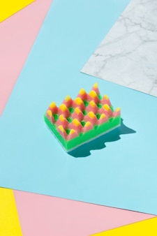 Creative layout with sponge for dishwashing on multicolor background. cleaning service concept