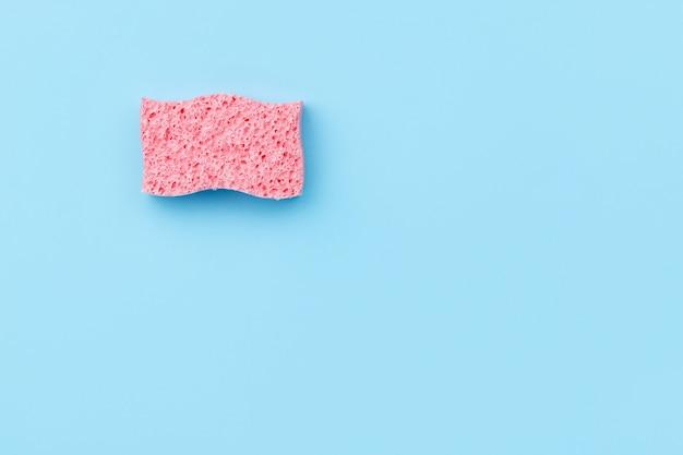 Креативный план с губкой для мытья посуды на синем фоне. концепция клининговых услуг