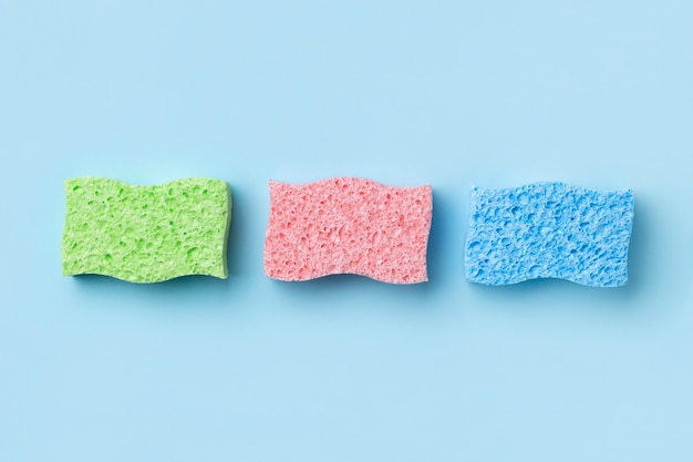 Creative layout with sponges for dishwashing on blue background. cleaning service template