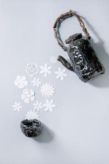セラミックのティーポットから灰色の壁の上のカップまで、さまざまな白い紙の花が流れるクリエイティブなレイアウト。フラットレイ、コピースペース。フラワーティー、夏または春の時間の概念