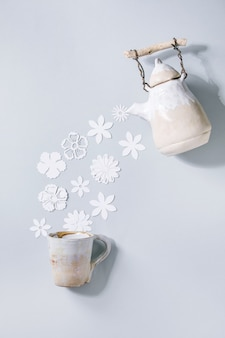 Creative layout with variety of white paper flowers flowing from ceramic teapot to cup over gray wall. flat lay, copy space. flower tea, summer or spring time concept