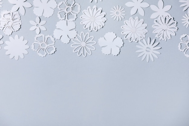 Creative layout with variety of white paper flowers over gray background. flat lay, copy space
