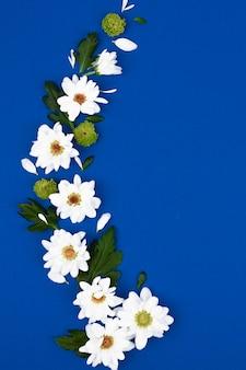 青い背景に白い花と緑の葉を持つ創造的なレイアウト。春のコンセプトです。フラット横たわっていた、トップビュー。