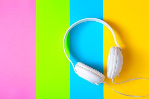 白いヘッドホンとカラフルな鮮やかな紙を使ったクリエイティブなレイアウト。抽象的な色アートの背景。ミニマルミュージックのコンセプト。フラットレイ。