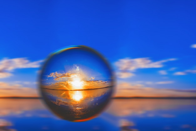 Creative lens ball photography of the sunlight on the horizon with clouds around in the blue sky
