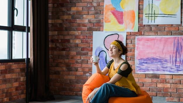 Творческий образ жизни. успешная художница сидит в мешке с фасолью и наслаждается перерывом на кофе