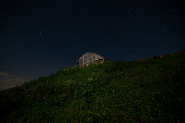 Creative light painting of an abandoned wooden cabin in rural artvin, turkey with blue hour sky - wide angle view