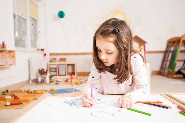 青い鉛筆で絵を描く創造的な少女