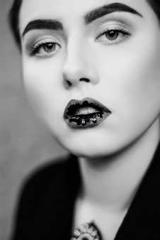 Creative make up of black liquid lips in close up black and white photo.