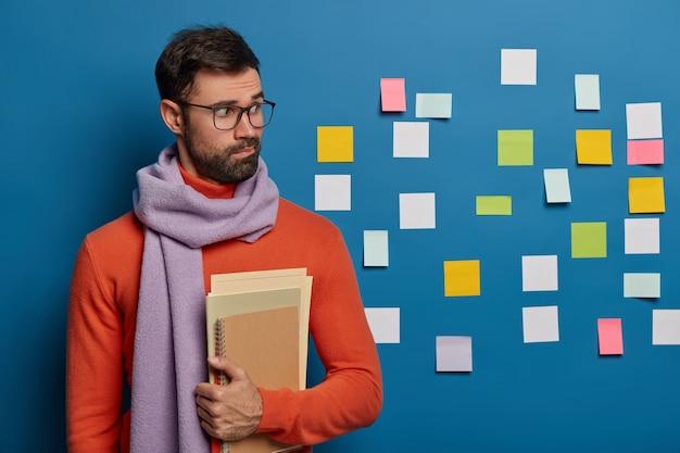 Designer maschio creativo in elegante maglione vivd e sciarpa viola intorno al collo