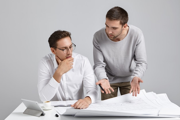 Creative male designer wears casual sweater, presents his ideas and designing project to employer,