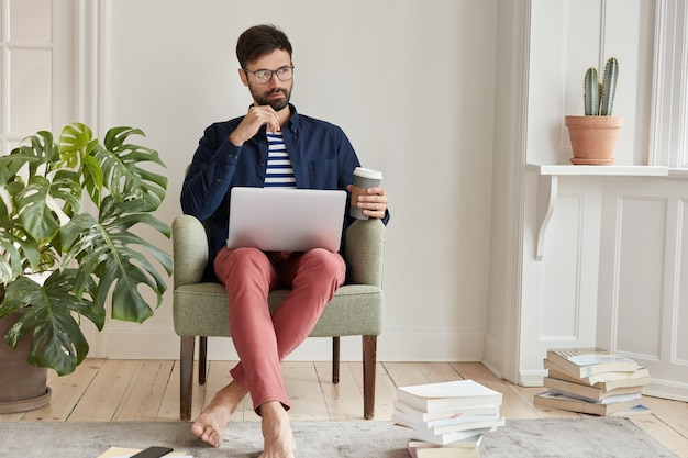 Creative male freelancer posing in cozy apartment