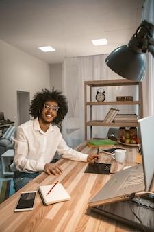 Творческий человек рад работать из дома. умный арабский парень улыбается сидя за столом с графическим планшетом и компьютером на нем в уютном интерьере домашнего офиса. тонированное изображение