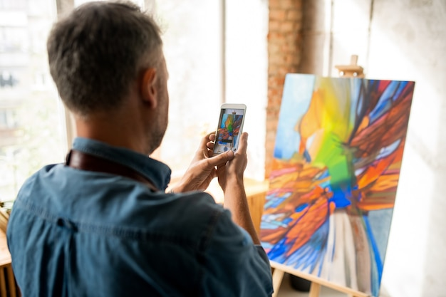 Creative man standing in front of painting on easel while taking its photo on smartphone after finishing artwork