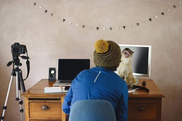彼の机の上に面白い猫と創造的な男