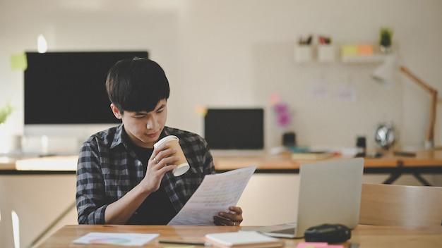 紙の色で作業し、創造性の職場でコーヒーカップを保持している創造的な男。