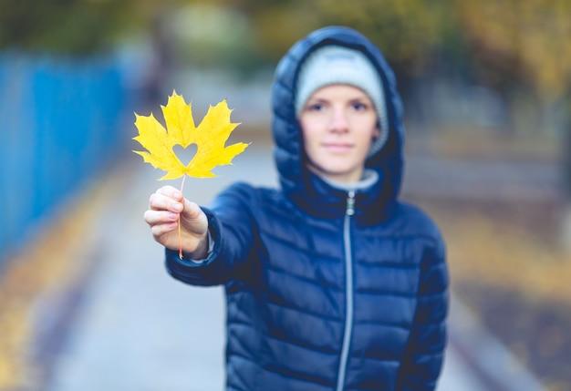 여자의 손에 크리 에이 티브 메이플 리프입니다. 가을 개념.