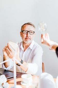 Creative mature man looking at a light bulb