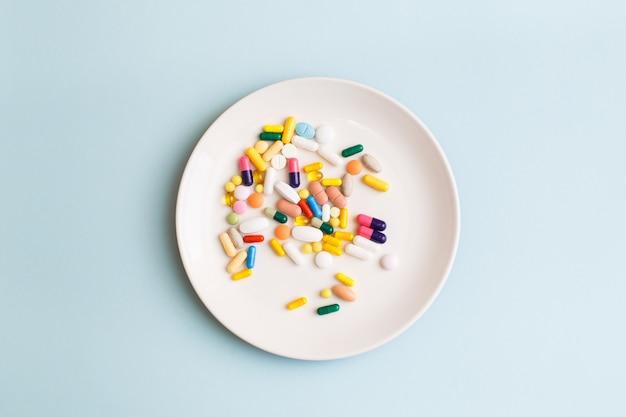 水色の背景の白いプレートにカラフルな錠剤、カプセル、サプリメントで作られた創造的な医療レイアウト。最小限の現代的な薬局またはヘルスケアの概念。フラットレイ、上面図、コピースペース。