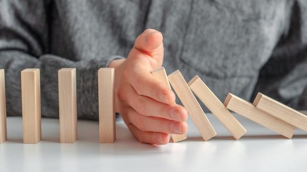 Креатив, мужская рука остановила эффект домино на белом деревянном