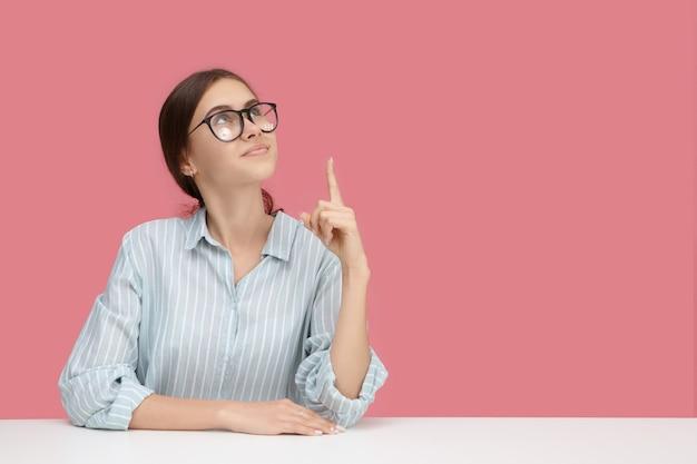 創造的な心、アイデア、教育、職業の概念。人差し指を上に向けて、空白のピンクの壁でポーズをとって青いシャツと眼鏡を身に着けているオタクのスマートな若い白人女性の写真
