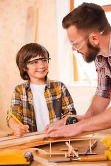 仕事で創造的な心。ワークショップで働いている間、若い男性の大工と彼の息子がお互いを見ている笑顔