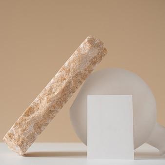 白紙のシートカード、バラの大理石の石、ニュートラルベージュの壁に白い花瓶を備えた創造的な最小限の美的コンセプト。