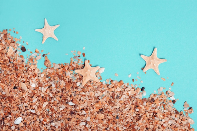 Creative minimal beach concept. sand and sea stars on mint colored background. summer flat lay