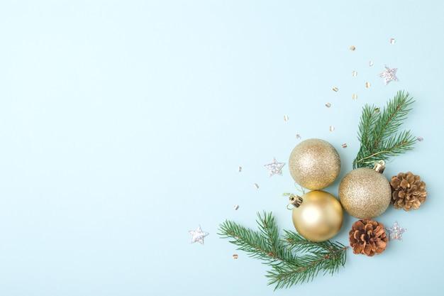 クリエイティブなミニマルなクリスマスアート作品。クリスマスボール、モミの枝、水色の背景に松ぼっくり。フラットレイ。スペースをコピーします。