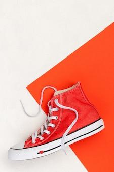 Творческая минимальная композиция с красными кроссовками на белом фоне. шаблон продажи модной одежды