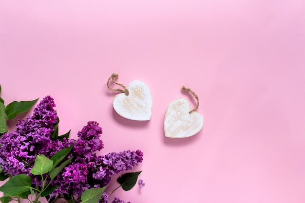 Creative minimalist banner with lilac flowers and white wood rustic heart on trendy pink background. web banner. top view, flat lay, copy space.
