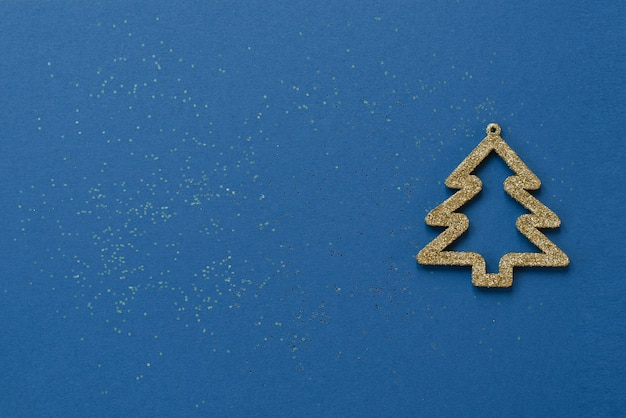 Creative minimalist christmas or new year card. gold christmas tree on a blue background with sequins. copy space for text or greetings