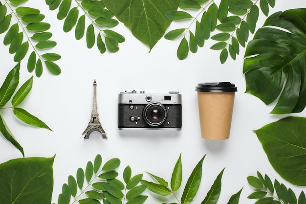 Creative minimalistic background travel to paris. retro camera, cup, eiffel tower figurine on white background with green leaves