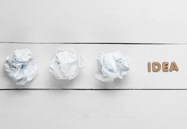 Creative minimalistic concept. crumpled paper balls on white wooden with word idea