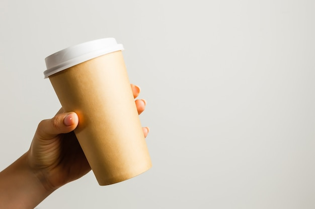 Creative mock up image of woman hand holding craft paper coffee cup with copy space isolated on white background in minimalism style. template for feminine blog, social media